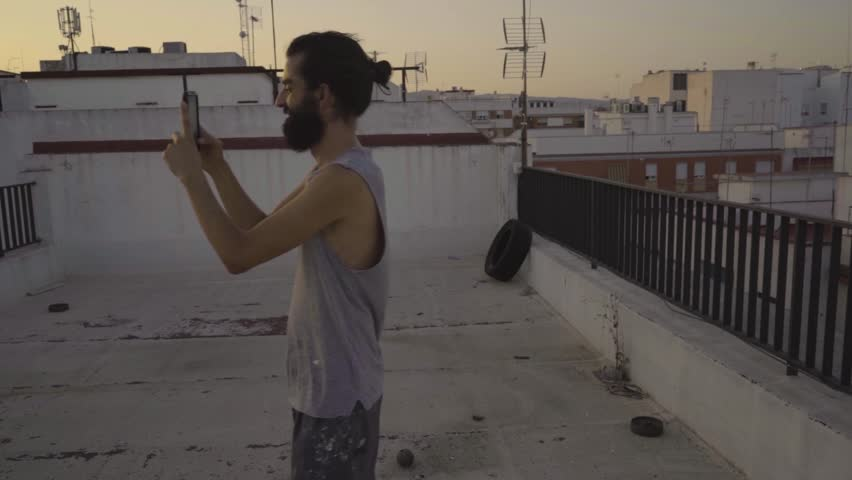 Man taking a picture with mobile at sunset on a rooftop | Shutterstock HD Video #1013668829