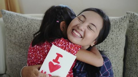 Daughter give mom the surprise greeting card,Concept of Mother day in slow motion footage