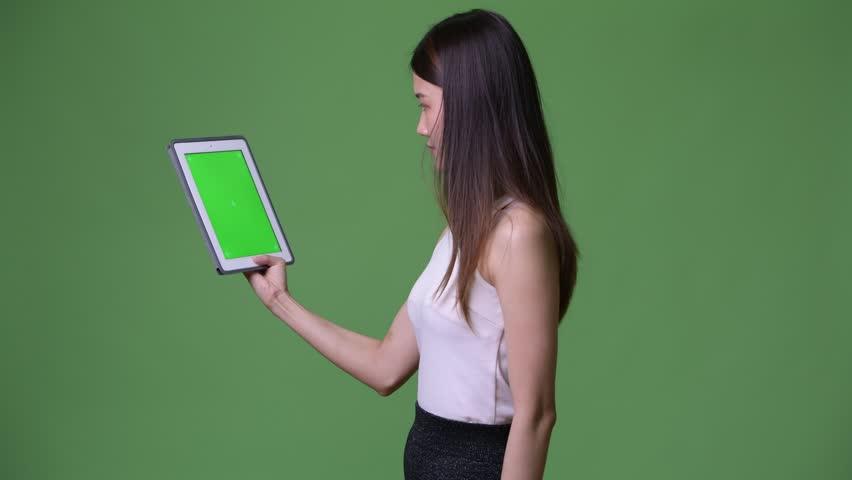 Young beautiful Asian businesswoman showing digital tablet | Shutterstock HD Video #1013692349