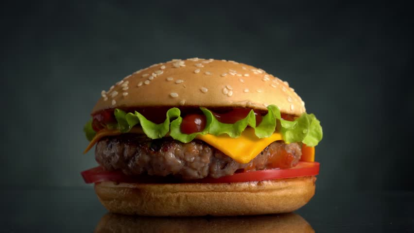 Beef Burger rotating on the table on a black background. | Shutterstock HD Video #1013704019
