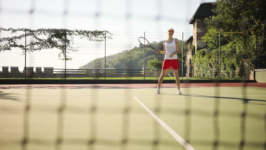 Smiling woman playing tennis, stretches her hand before pitching the ball. Active lifestyle, sportsman, having fun. Female portrait #1013715149