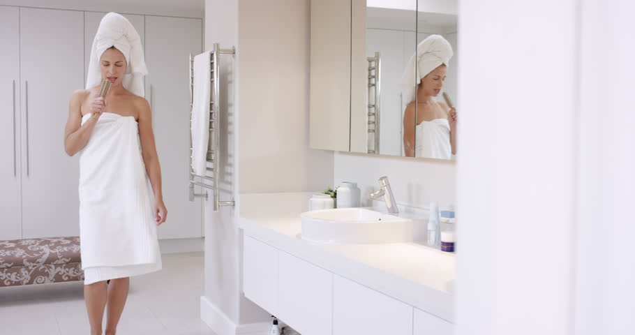 Beautiful woman singing in bathroom wearing white towel dancing in front of  mirror RED EPIC DRAGON. Beautiful Woman Singing In Bathroom Wearing White Towel Dancing In