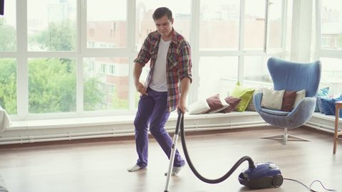 Funny man doing the cleaning vacuums and have fun dancing