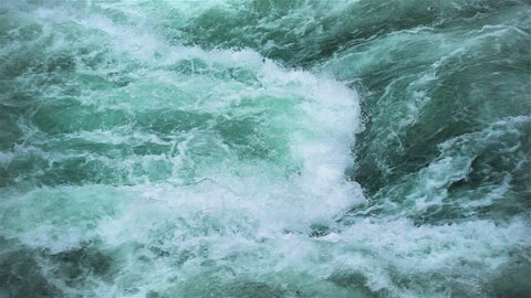 Slow motion rapids water clashing in river. Close up abstract background of crashing flowing water in slowmo.