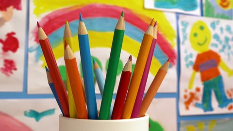 Color Pencils In Classroom With Paintings On Wall