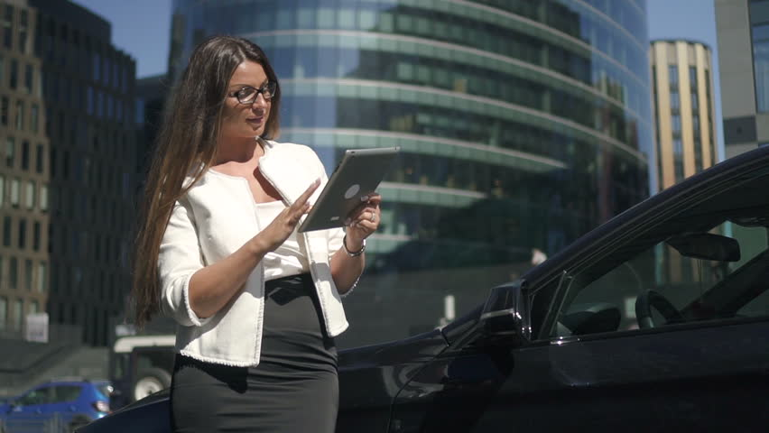 Young businesswoman with long hair surfing the internet on brand-new tablet, standing near expensive black car in business district. Outdoors. Portrait. | Shutterstock HD Video #1013757029