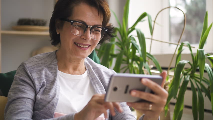 Happy mature woman in glasses smiling and waving her hand, having video call with family members on her brand new smartphone at home. Indoors. Portrait.