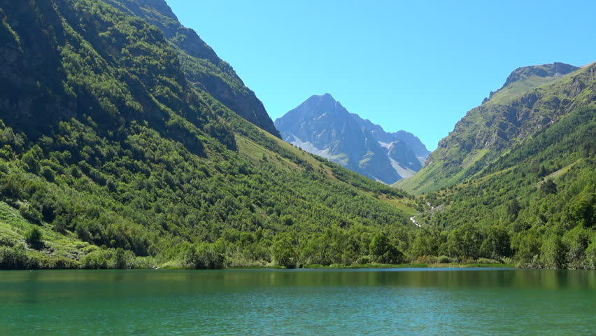 View lake scenes in mountains, national park Dombai, Caucasus, Russia, Europe. Summer landscape, sunshine weather, blue sky and sunny day. 4K footage, video camera format 3840x2160 | Shutterstock HD Video #1013761859