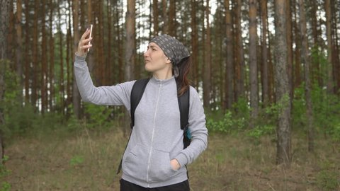 Young woman in the forest trying to catch a mobile signal.