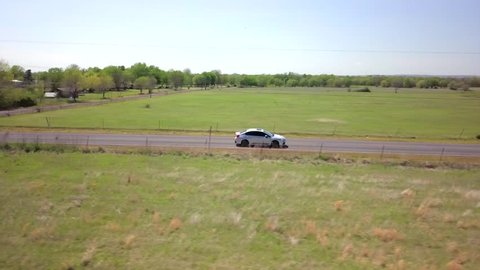 Profile aerial shot of a Subaru WRX shoot down a rural road.