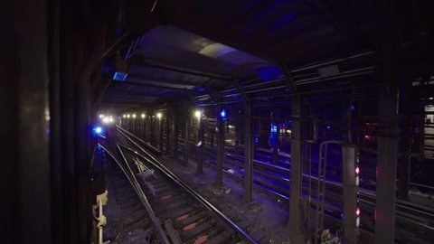 Close-up of New York subway train passing deep inside tunnel. Colorful NYC underground restricted area of metro tunnel. Moving trains between stations in mass transit system.