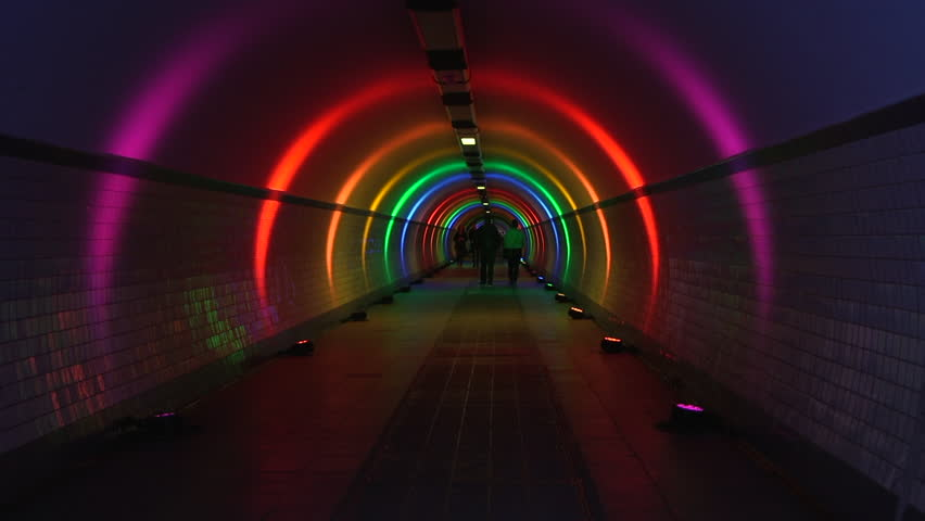 Antwerp, Belgium - 06 11 2018: People walking through pedestrian tunnel in Antwerp on Juin 12 2018, lighted in rainbow colours for gay,lesbian awareness #1013785139