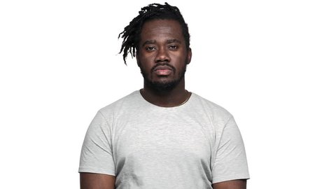 Portrait of concentrated dark skinned guy with afro pigtails thinking about choice or decision while reflecting or doubting, isolated over white background slow motion. Concept of emotions