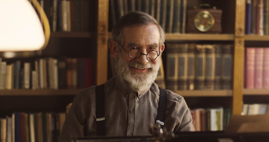 Portrait of the smiling old man looking to the camera and taking off his glasses while sitting in the library room. | Shutterstock HD Video #1013806439