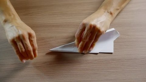 woman is stroking folds of paper origami airplane on a table and throwing it to fly in room