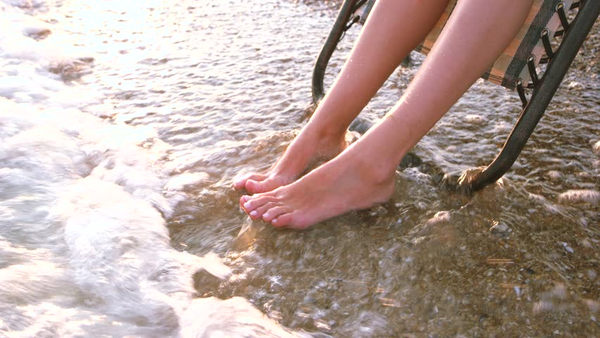Washing legs in sea water on the shore. Close up girl's feet enjoy sea water. #1013820449