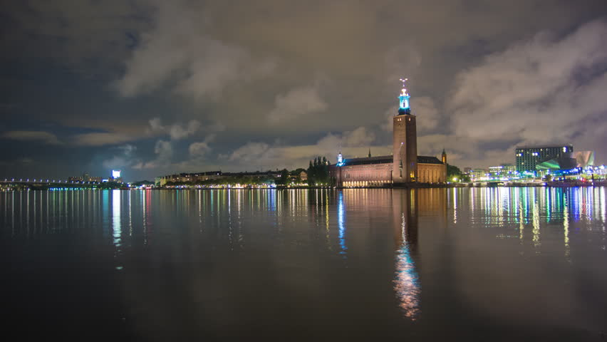 4K Time Lapse Tilt of Stockholm City Hall building at night. Town Hall famous landmark, nobel prize award ceremony. Beautiful water reflections, Capital city of Sweden