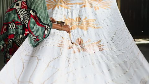 Bangladesh textile worker painting on pattern to white cloth