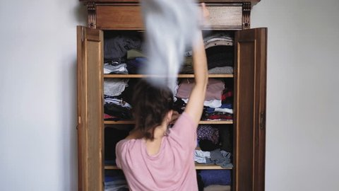 Angry young woman is throwing clothes from old retro vintage wooden wardrobe and after unsuccessful clothes search, view from back, shot in 4K UHD