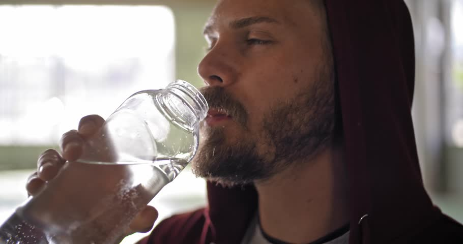 Young adult man with hooded sweatshirt drinking water resting during fitness sport workout .Grunge industrial urban training.4k slow motion video