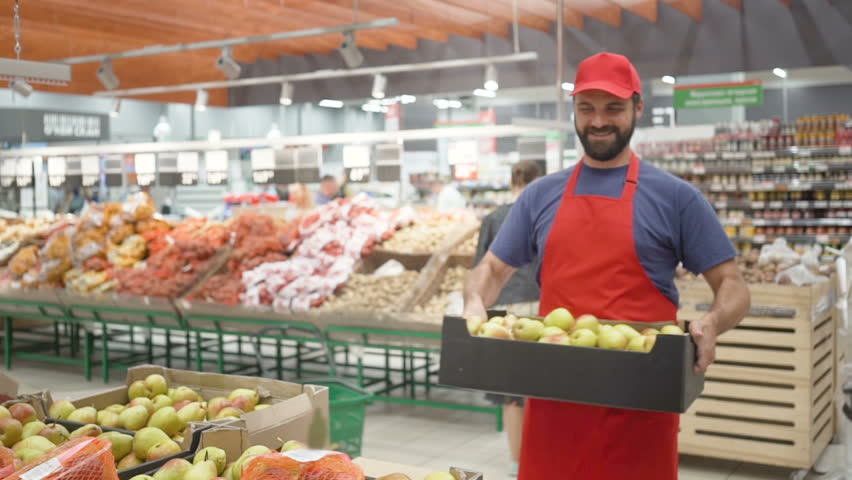Male supermarket clerk filling up box with pears in vegetable department | Shutterstock HD Video #1013872709