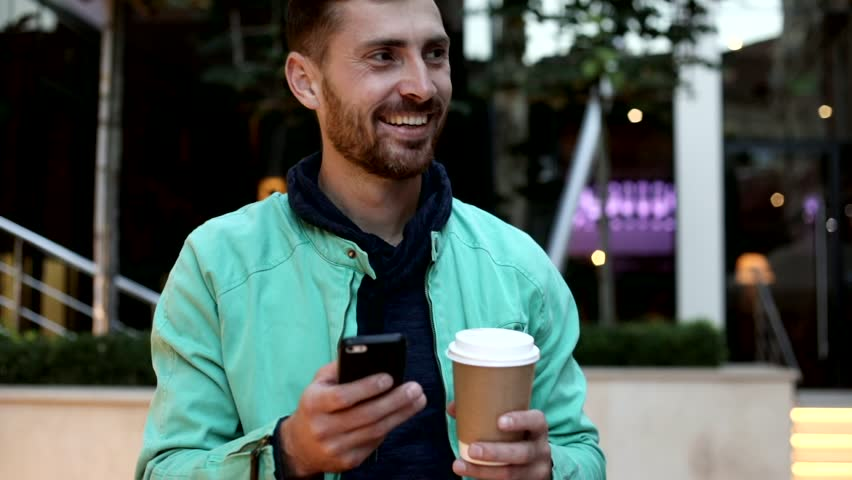 Sincerly Smiling Young Man Walking in the City. Holding Modern Mobile Phone in his Hands. Drinking Delicious Coffee. Huge Glass Building on the Background. Smiling Happily. | Shutterstock HD Video #1013876879