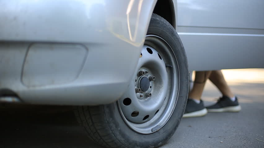 Man compressor pump pumps the front wheel of the car. | Shutterstock HD Video #1013877359