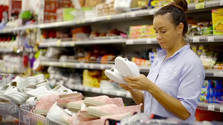Female customer choosing casual shoes in a supermarket. | Shutterstock HD Video #1013886479