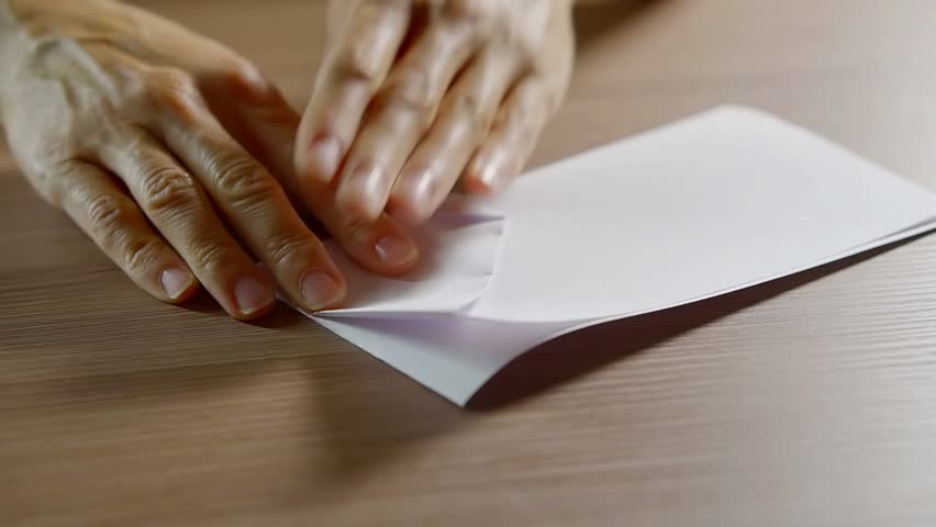 Close up shot of a woman doing an origami using white paper.