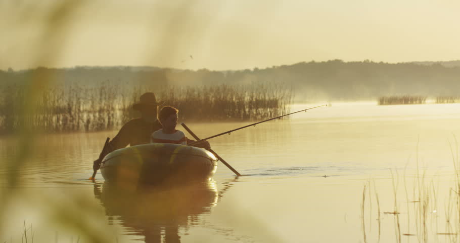 Senior angler with a grandson oaring while floating in a boat during fishing. Outdoors. | Shutterstock HD Video #1013887859