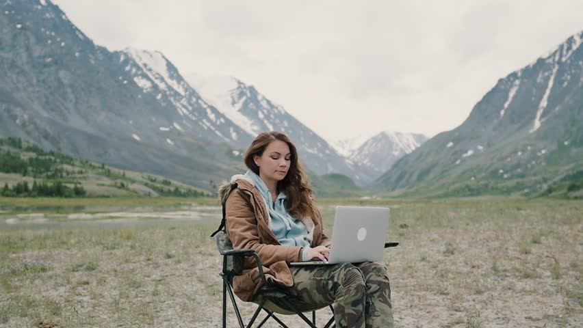 Girl working on laptop in high mountain