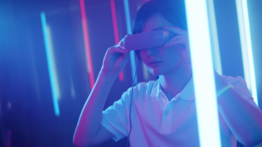 East Asian Pro Gamer Puts On Virtual Reality Headset Plays Online Video Game with Joysticks / Controllers. Cool Retro Neon Colors in the Room. Shot on RED EPIC-W 8K Helium Cinema Camera.