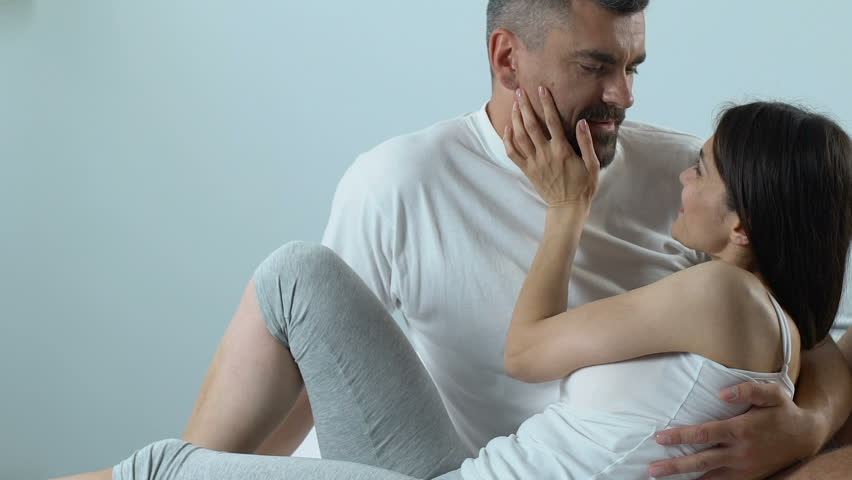 Love couple in bed choosing condom, safe sex infection prevention, birth control