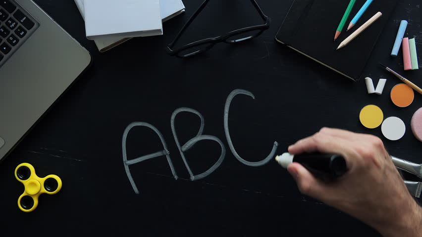 Teacher writing ABC on school blackboard in chalk, education and literacy, Top down view directly above the chalkboard.