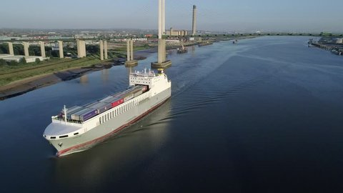 Drone flies back tracking the ro-ro cargo ship Adeline. Queen Elizabeth II Bridge is in the background