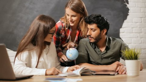 Three close friends deciding on country to visit with the help of small globe, using travel guide to learn more information about fastinating location, indoor shot at work place during lunchbreak
