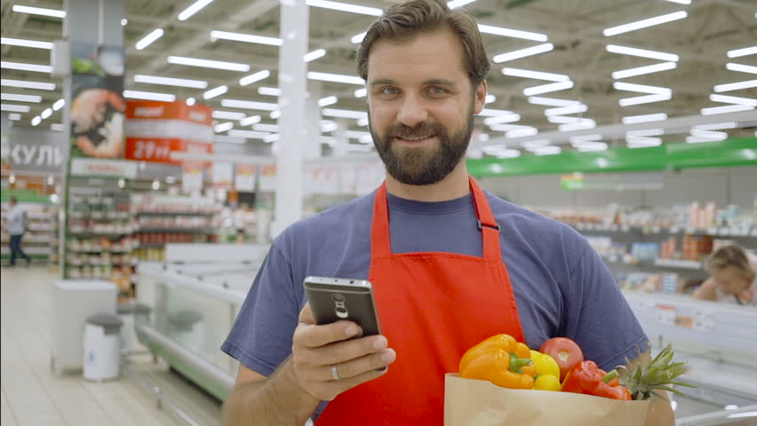 Smiling supermarket employee using mobile phone and holding shopping bag in supermarket | Shutterstock HD Video #1013968709