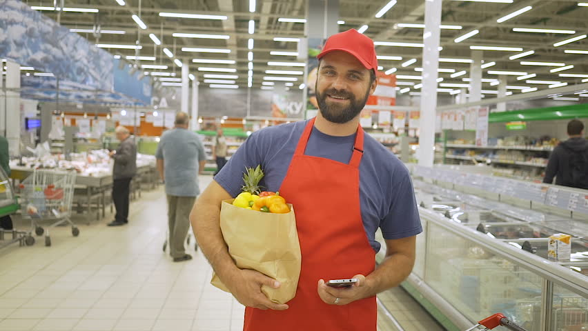 Handsome delivery man in red uniform with paper bag standing in supermarket, he is smiling at camera | Shutterstock HD Video #1013971769