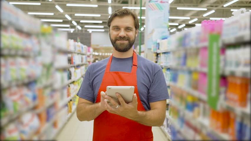 Handsome smiling supermarket employee with beard using digital tablet standing among shelves In supermarket | Shutterstock HD Video #1013987489