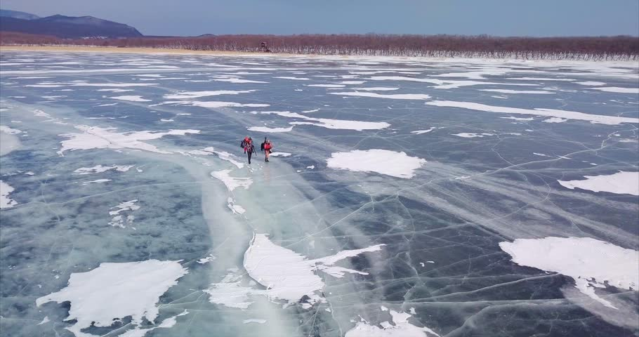 Beautiful aerial view of frozen lake and two photographers of wild nature with photography equipment walk along the ice. Lake Blagodatnoe in the Sikhote-Alin Biosphere Reserve in Russia