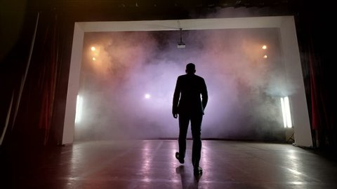 Showman. Young male entertainer, presenter or actor on stage. Back, arms to sides, smoke on background of spotlight. Rear view of a male public speaker speaking at the microphone, pointing, in the