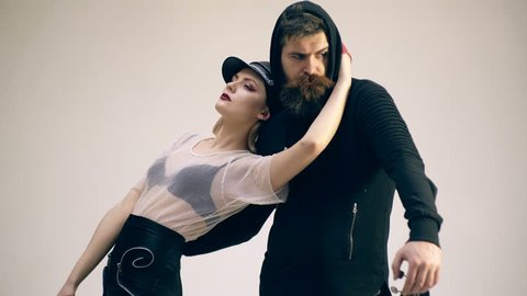 Fashion rock and roll couple standing with electric guitar on grey background. The girl strokes her boyfriend for a beard. Rock and roll couple concept