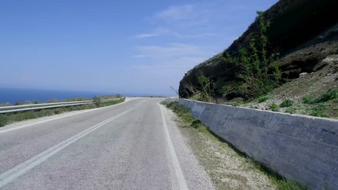 Pov shot of car driving on country road over a mountain with ocean and sea down in background