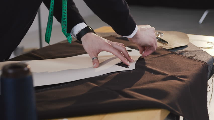 Fashion designer or tailor working with fabric at the studio full of tailoring tools. Pattern, scissors, tape measure, and a sewing machine. Workplace of seamstress. Tailor is drawing sketch lines on