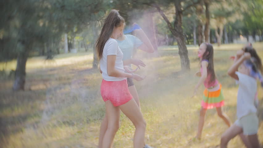 A group of little girls having fun and throw each other with colored Holi powder festival of colors Holi