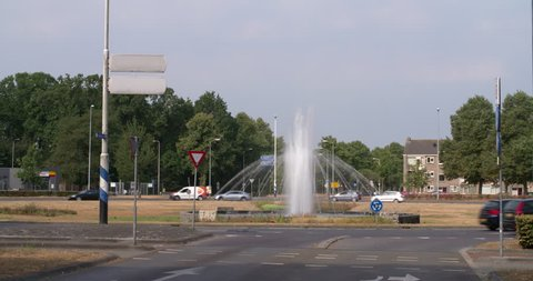 Eindhoven, Noord-Brabant / Netherlands - July 24 2018: Fountain squirting water during extreme dry summer with burnt grass at roundabout Eindhoven, Netherlands, 4K