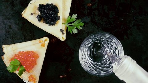 Slow motion pour vodka according to Russian traditions with pancakes with red and black caviar on a dark background top view