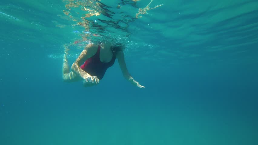 Young woman swims down in a blue clear sea. Slow motion 120 FPS #1014116819