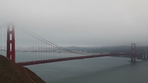 4K Time lapse close up Golden Gate Bridge at dawn surrounded by fog with San Francisco Skyline in the background