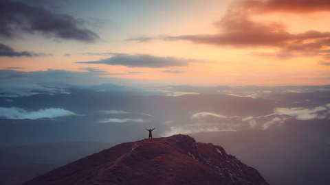 Man stand on top of mountain with hands raised up. Sunrise sunset soft light. Majestic nature landscape. Morning fog and clouds flow. Lifestyle, holidays, travel, recreation. Slow motion 4K Time Lapse
